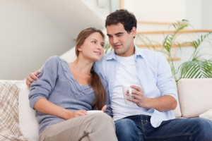 Couple watching TV while drinking coffee